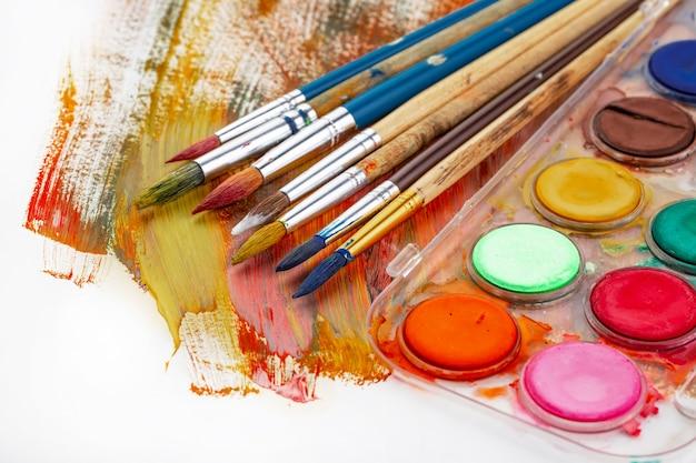 Краски и кисти на окрашенном фоне