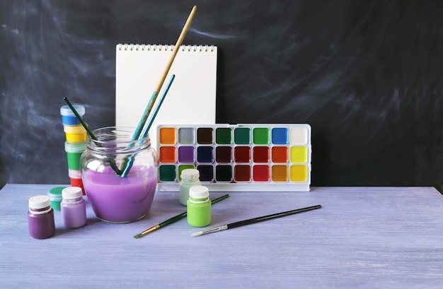 Paints brushes water on a wooden table against the background of a chalkboard back to school