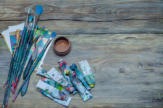 Paints and brushes on wooden table background
