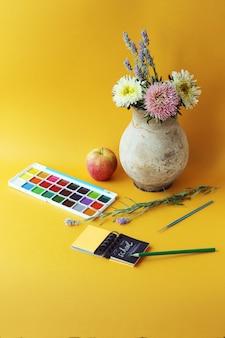 Краски, тетрадь и карандаши, ваза с цветами, концепция обучения, снова в школу