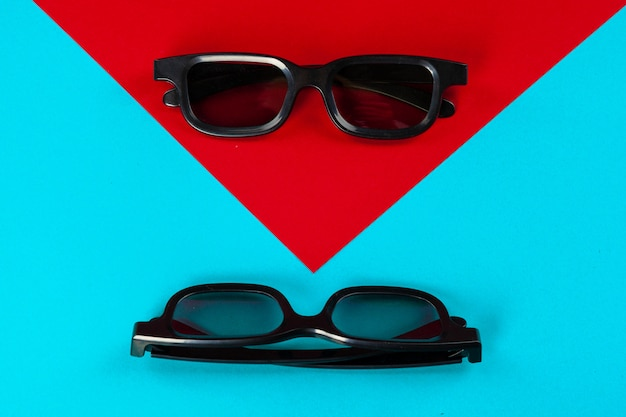 Pair 3d glasses on blue . flat lay.