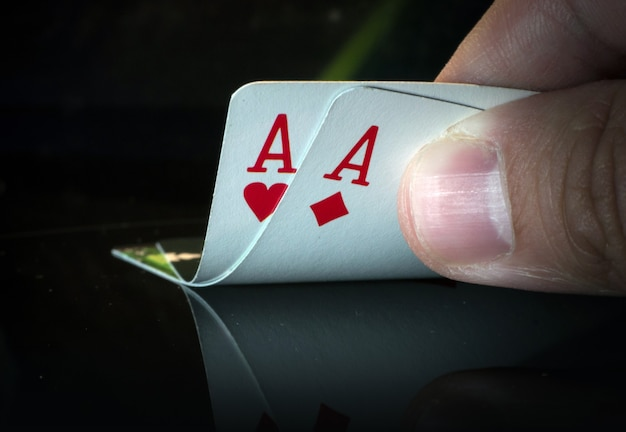 A pair of aces on a black background in hand from puckerman. winning the game of cards. playing cards in good combinations.