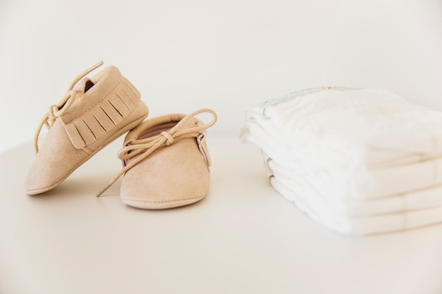 Pair of baby shoes and stacked of diaper on beige background