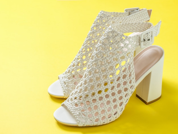 A pair of beautiful women summer shoes on yellow background. summer shoes for women.