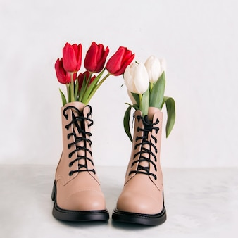 A pair of beige shoes with flowers on a white background. spring concert.