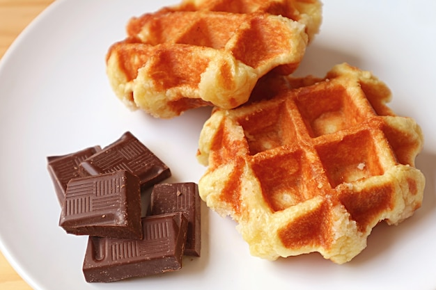 Pair of belgian liege waffles with chunks of belgian dark chocolate on a white plate