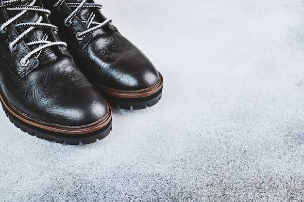 Pair of black genuine leather boots. light background