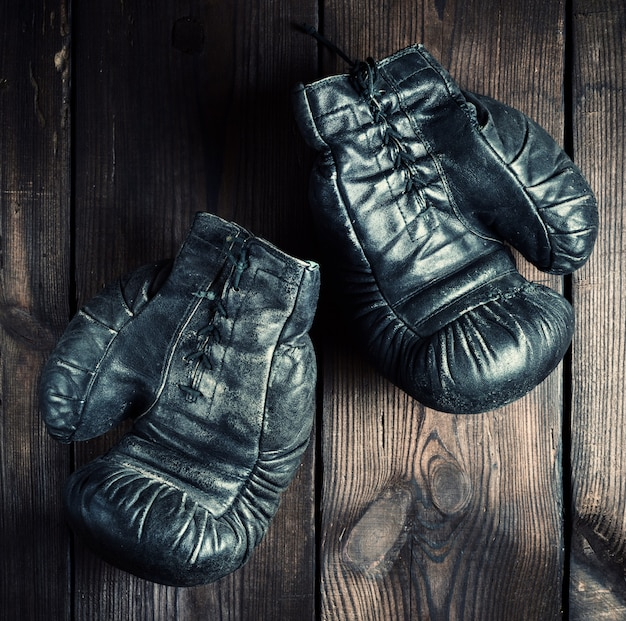 Pair of black leather very old boxing gloves