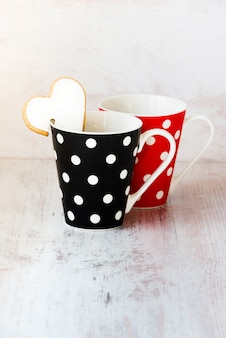 A pair of black and red  polka dotted coffee cups.