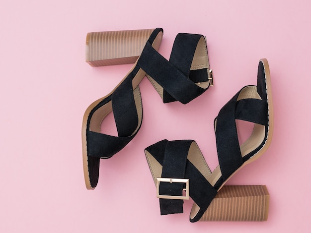 A pair of black summer shoes with high heels on a pink surface