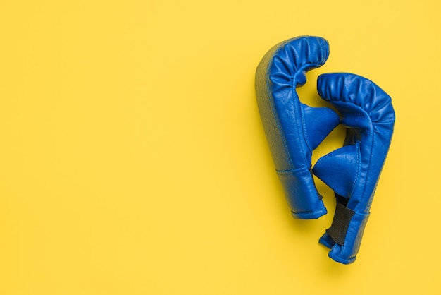 Pair of blue boxing training gloves on yellow background. sports, training, martial arts, fitness theme
