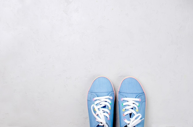 A pair of blue canvas sneakers on grey concrete background