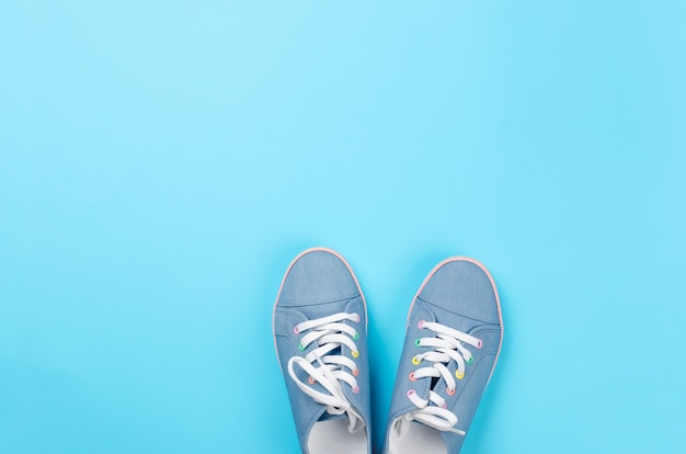 A pair of blue canvas sneakers on light blue background