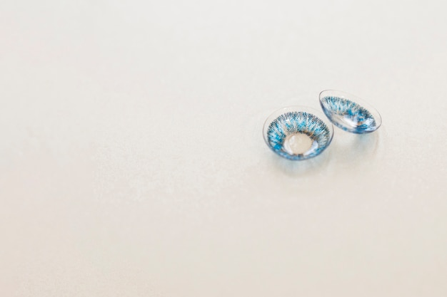 Pair of blue contact lenses on gray  background