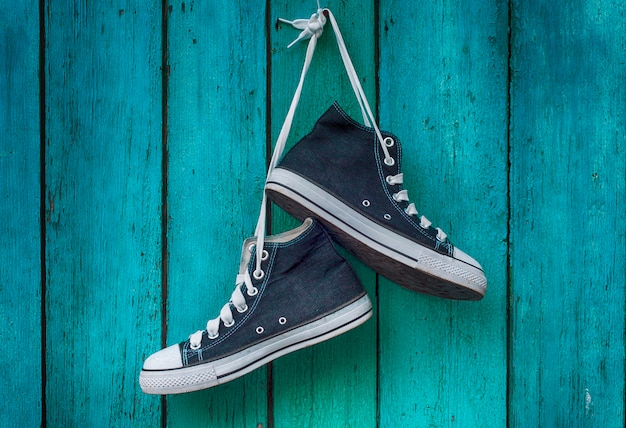 Pair of blue men's sports sneakers hanging from a nail on the wall of the old shabby green