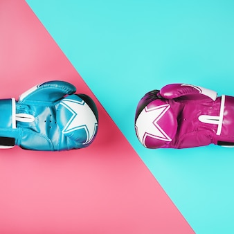 A pair of blue and pink boxing gloves on a blue and pink background