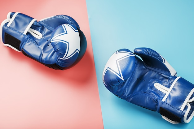 A pair of blue and pink boxing gloves on a blue and pink background.