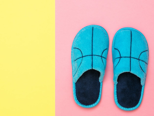 A pair of blue slippers on a pink surface next to a yellow surface. comfortable home shoes. flat lay.