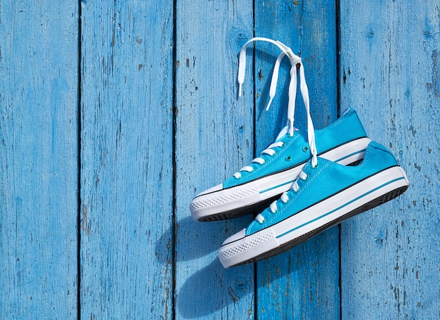 Pair of blue textile sneakers hanging on a nail