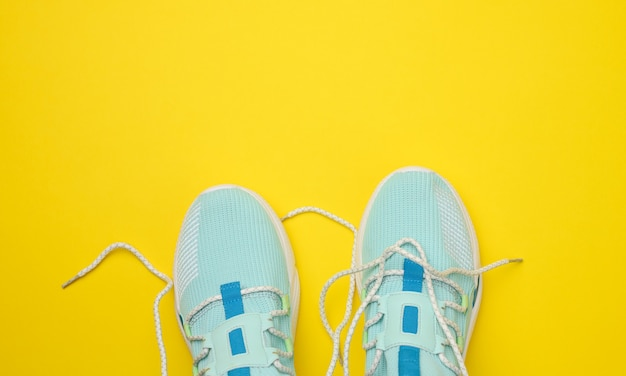 Pair of blue textile sneakers on yellow background, top view