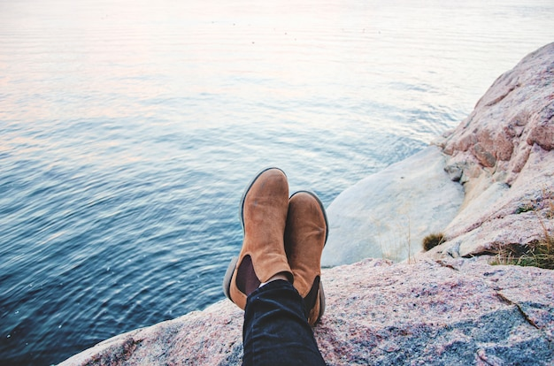 A pair of boots resting on a mountain in front of the sea