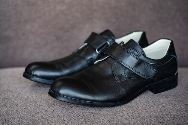 Pair of brand new black leather shoes for children on grey background.
