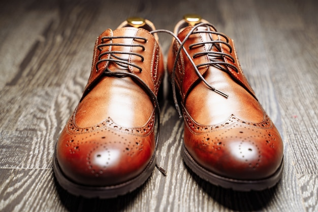 Pair of brown leather men's shoes on the wooden floor.