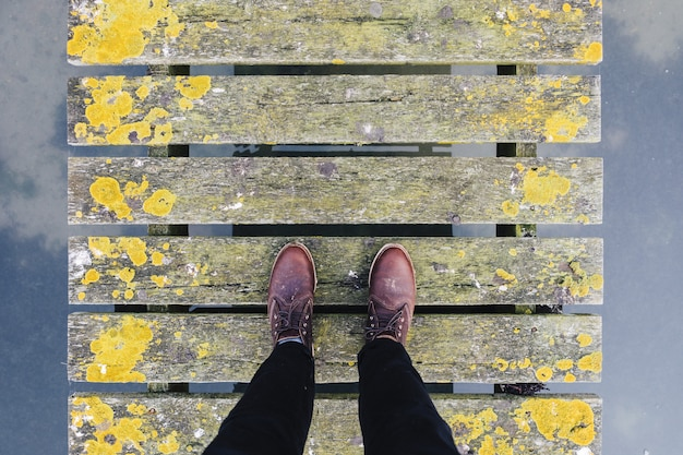 Pair of brown leather shoes standing on an old grey and yellow bridge