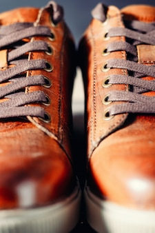 Pair of brown male shoes with laces as background close up, selective focus