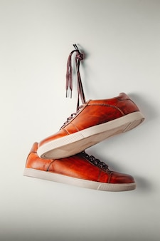 Pair of casual brown shoes hang on nail on white background