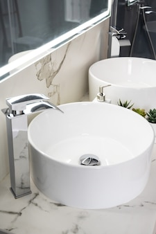 Pair of ceramic water basins in the interior of light modern bathroom with a mirror with light