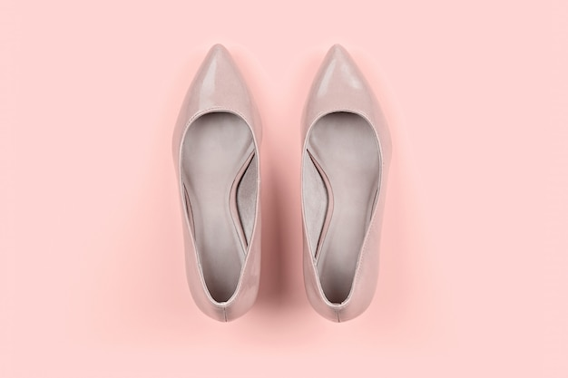 Pair of classic women's beige shoes on pink