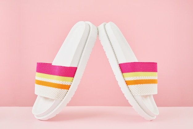 Pair of colorful multicolored rainbow flip flops or sandals on pastel background.