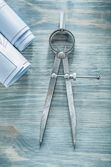 Pair of compasses blueprints on wooden board construction concept