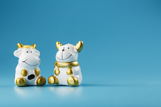 A pair of cow and bull figures on a blue background