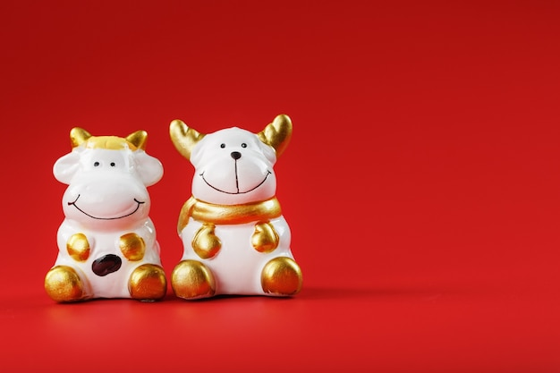A pair of cow and bull figures on a red background, with free space