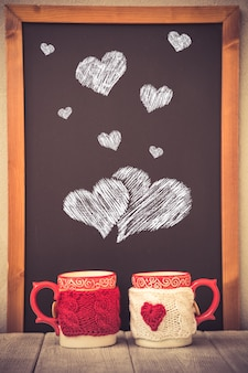 Pair of cups against blackboard background. valentines day ornament. greeting card