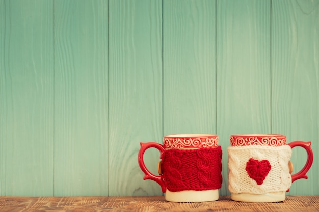 Pair of cups against emerald wooden background. valentines day ornament. greeting card