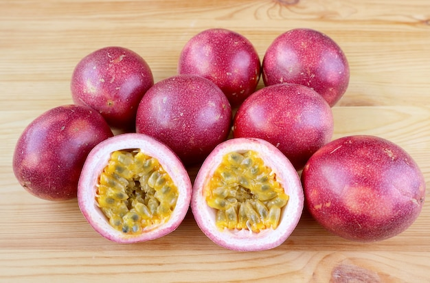 Pair of cut in half fresh ripe passion fruit with a pile of whole fruits isolated in background
