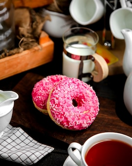 A pair of donuts with pink cream and candies