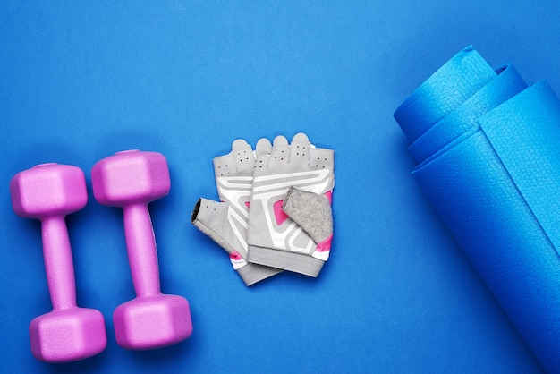 Pair of dumbbells, sports gloves and blue sports mat