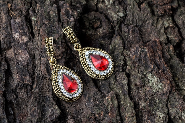 Pair of earrings on wooden background