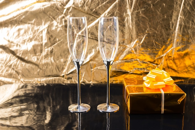 Pair of empty elegant champagne glasses on shiny black table beside gift wrapped in gold paper with bow in front of textured metallic gold background