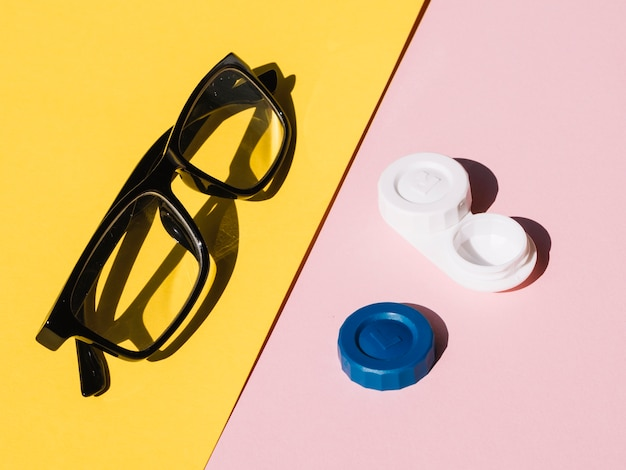 Pair of eyeglasses and contact lenses on yellow and pink background
