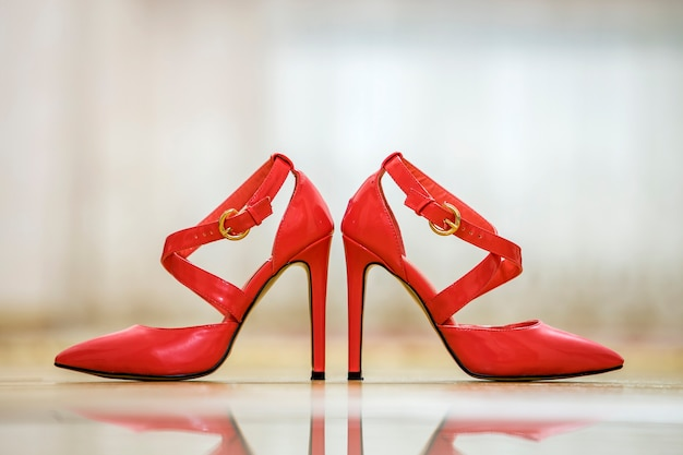 Pair of fashionable high heel leather red cut-out female shoes with golden buckles isolated on light copy space background. style and fashion, modern footwear concept.
