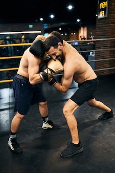 Pair of fighters in the ring punching one another in a close distance