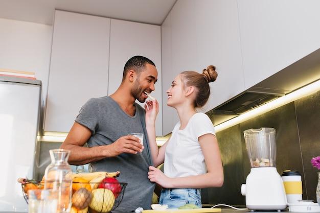 キッチンでいちゃつくペアと彼らの愛を示しています。妻は夫に果物を試してもらい、tシャツを持ち続けます。お互いを見て情熱と幸福のカップル。健康的な食事のファン。