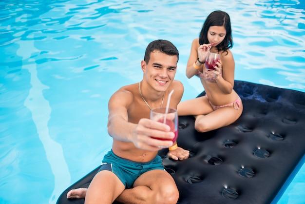 Пара плавает на надувном матрасе в бассейне, пьет коктейли и развлекается на летних каникулах