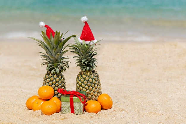 A pair of funny attractive pineapples in new year's hats on the sand against the background of the turquoise sea.