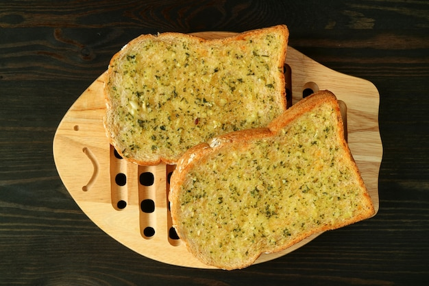 Pair of garlic butter toasts on wooden plate served on dark